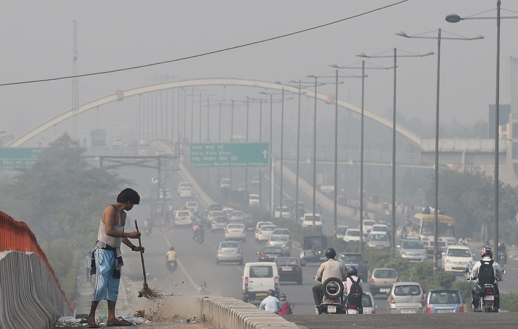 A sweeper working beside a smog filled road.