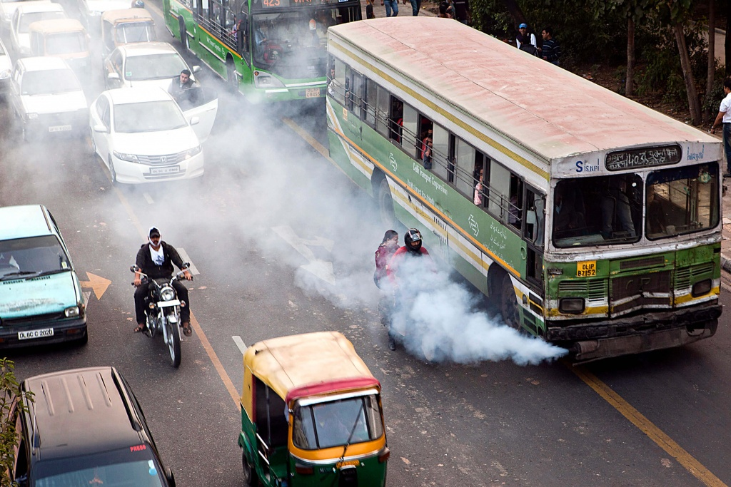 Pollution: An old public bus release excessive smoke onto a motorbike