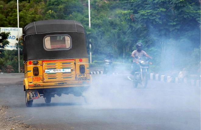 Pollution: an old auto rickshaw releases excessive smoke