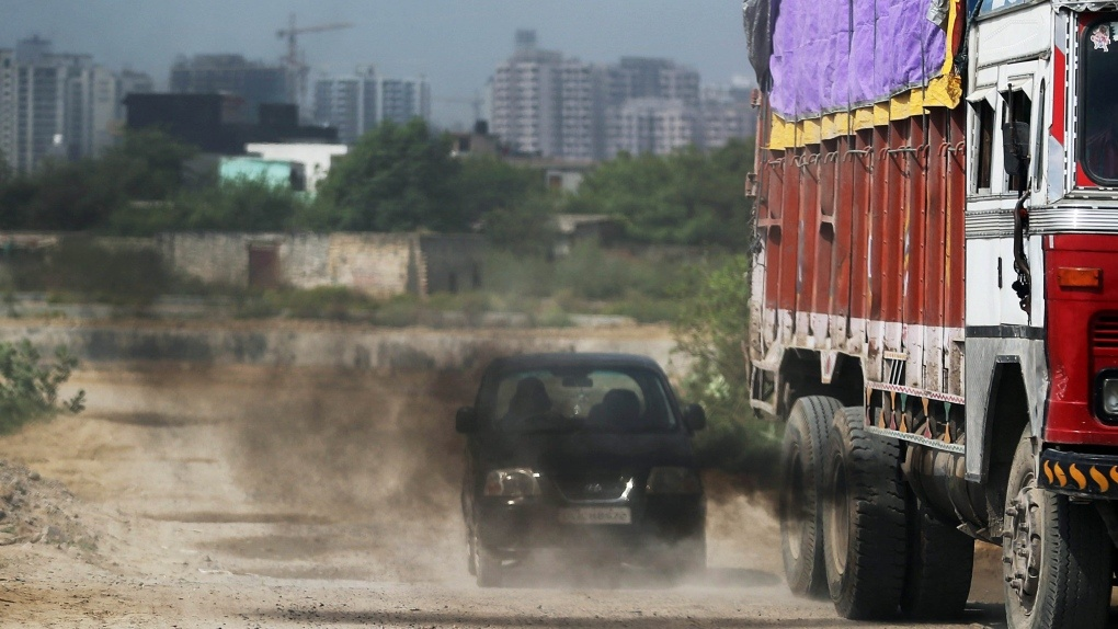 Pollution: An old truck releases excess smoke in front of a car.